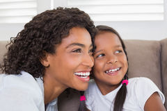 Pretty mother sitting on the couch with her daughter Stock Photo