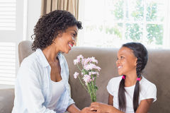 Pretty mother sitting on the couch with her daughter offering flowers Royalty Free Stock Images