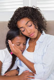 Pretty mother sitting on the couch with her sleeping daughter Royalty Free Stock Image