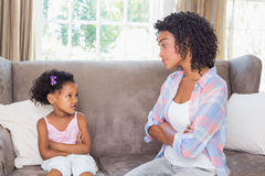 Pretty mother sitting on couch with petulant daughter Stock Images