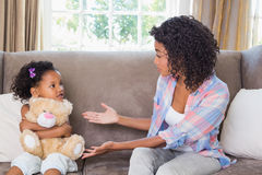 Pretty mother sitting on couch with petulant daughter Royalty Free Stock Image