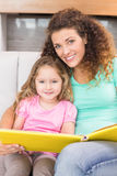 Pretty mother sitting with her little daughter reading a storybook Royalty Free Stock Images