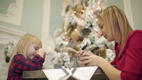 Pretty mother and small daughter in red dresses sitting at the table near Christmas tree. stock video footage