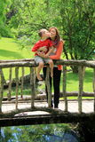 Pretty mother and son standing on wood bridge Stock Photo