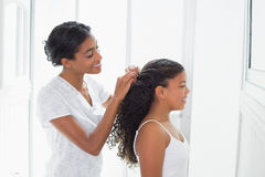 Pretty mother tying her daughters hair back Royalty Free Stock Image
