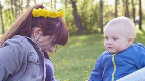 Young woman with a wreath of dandelions on her head plays and has fun with her little son in blue jacket on the grass in stock footage