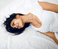 Pretty mulatto brunette woman in bed, cant sleep Stock Photography