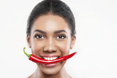 Pretty mulatto girl is eating spicy pepper Royalty Free Stock Image