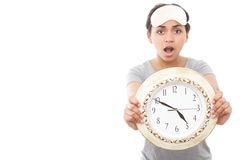 Pretty mulatto girl posing with clock. Time is running. Portrait of young amazed woman showing big clock on white isolated background Stock Photography