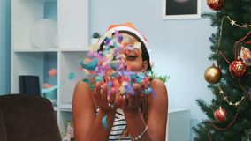 Pretty mulatto girl in Santa hat blowing shiny confetti at camera. Near the Christmas tree while celebrating Christmas holidays stock footage