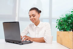 Pretty mulatto girl working on computer Stock Images