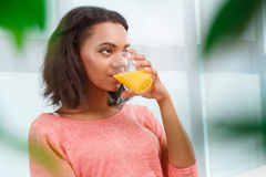 Pretty mulatto woman drinking orange juice Stock Images