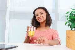 Pretty mulatto woman with juice. Freshly made. Pretty young mulatto girl sitting at desk in office with glass of orange juice Stock Photography