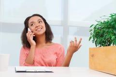 Pretty mulatto woman talking per mobile phone Royalty Free Stock Photos