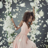 Pretty mulatto woman among white petals Royalty Free Stock Image