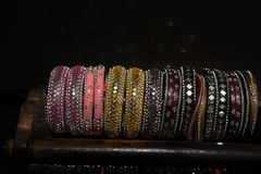 Pretty multi color fashionable glass bangles with tiny reflection of glasses on black floor Stock Photo