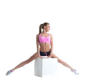 Pretty muscular athlete doing split on cube Royalty Free Stock Photography