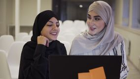 Pretty muslim businesswomen in hijab at office workplace or conference hall. Two smiling arabic woman working on laptop. On startup project together, discussing stock footage