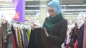 Pretty Muslim girl in hijab picks clothes in store. A pretty Muslim girl in blue hijab and glasses chooses clothes in a store stock footage