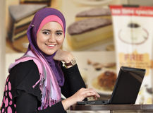 Pretty Muslim girl with laptop. At cafe royalty free stock photos