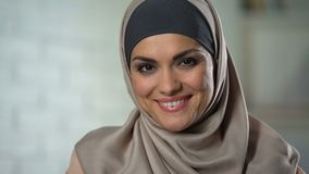 Pretty muslim housewife in her 30s looking at camera, female wellness, happiness