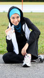 A pretty muslim woman athlete resting while drink. A mineral water at stadium track Stock Photography