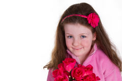 Pretty n pink. Young girl holding a bunch of artifical roses and looking at the camera Stock Photography
