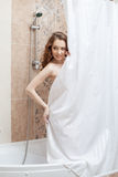 Pretty naked woman hiding behind shower curtain Stock Images