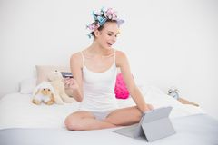 Pretty natural brown haired woman in hair curlers shopping online with her tablet pc Stock Image