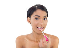 Pretty natural model applying glossy lipstick Stock Images