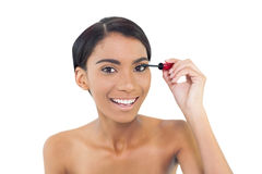 Pretty natural model applying mascara Stock Images