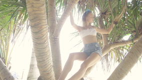 Pretty naturally looking woman on a beautiful summer day between palm trees stock video