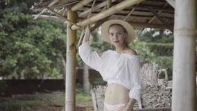 Pretty naturally looking woman in boho style fashion wearing white shirt, bikini and hat on a beautiful summer day. stock video