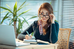 Pretty nerd girl studies. Young woman in glasses surprised after what she saw in laptop Royalty Free Stock Images