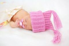 Pretty newborn girl sleeping in knitted cap. Stock Image
