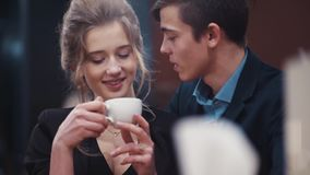 A pretty nice girl drinking coffee on a date and listening to her young boyfriend who is then kissing her. A pretty nice girl drinking coffee on a date and stock footage