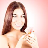 Pretty nice woman with pink flower in hands on pink background. Smiling woman with white teeth. Stock Photo