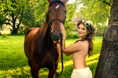 Pretty nude woman with horse. Young pretty nude brunette woman with horse in summer forest stock image