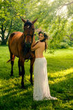 Pretty nude woman with horse. Young pretty nude brunette woman with horse in summer forest stock images