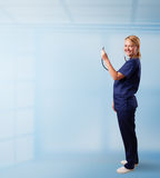 Pretty nurse in hospital listening to empty copy space with sthe Stock Photography
