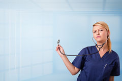 Pretty nurse in hospital listening to empty copy space with sthe Royalty Free Stock Photo