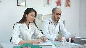 Pretty nurse and male doctor talking to the patient stock video