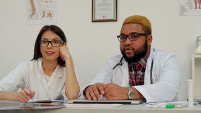 Pretty nurse and male doctor talking to the patient stock video footage
