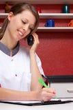 Pretty nurse on phone  recorded data Stock Photo