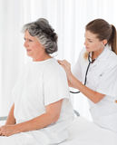 Pretty nurse taking the heartbeat of her patient Royalty Free Stock Photos