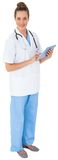 Pretty nurse in tunic using tablet pc Stock Photography