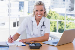 Pretty nurse working in her office. On her desk Royalty Free Stock Images