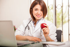 Pretty nutritionist with an apple. Cute young nutritionist in a lab coat holding an apple in her hand and smiling Royalty Free Stock Photo