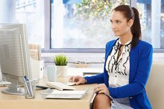 Pretty office worker at desk royalty free stock photos