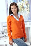 Pretty office worker smiling in orange pullover. In bright office Royalty Free Stock Photography